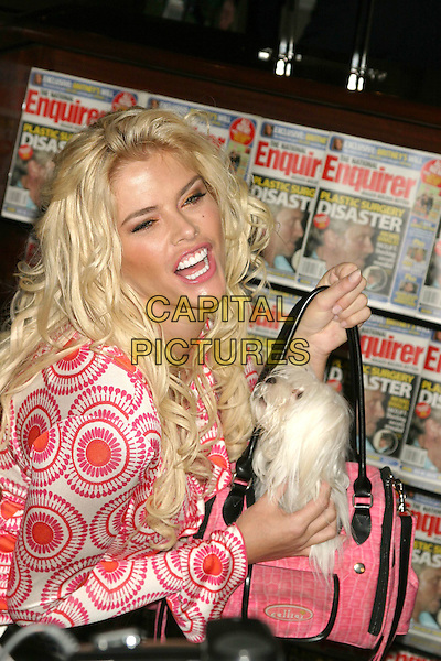 ANNA NICOLE SMITH.Signs autographs at the re-launch of The National Enquirer Hudson News in Grand Central Station, New York City, USA, April 7th 2005..half length holding dog animal pet in pink bag mouth open teeth funny face.Ref: IW.www.capitalpictures.com.sales@capitalpictures.com.©Ian Wilson/Capital Pictures.