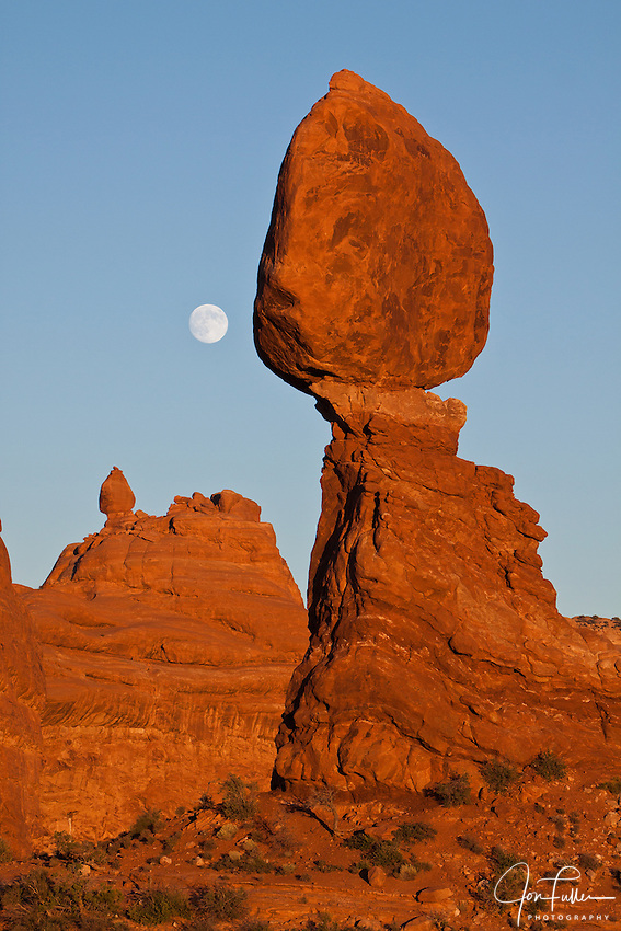 The full moon rises behind Balanced Rock in Arches National Park near Moab, Utah at sunset.  Ham Rock, in the background, mimics Balanced Rock's form.