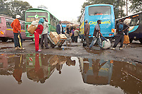 Commuters leave the buses, while others board them at the Railways terminus in downtown Nairobi, Kenya on a rainy morning.