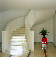 A red Eames chair at the foot of a contemporary staircase with glass steps