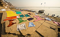 Wet clothes dyed in bright colors are spread out on the ground to dry after being washed in the Ganges. (Photo by Matt Considine - Images of Asia Collection)