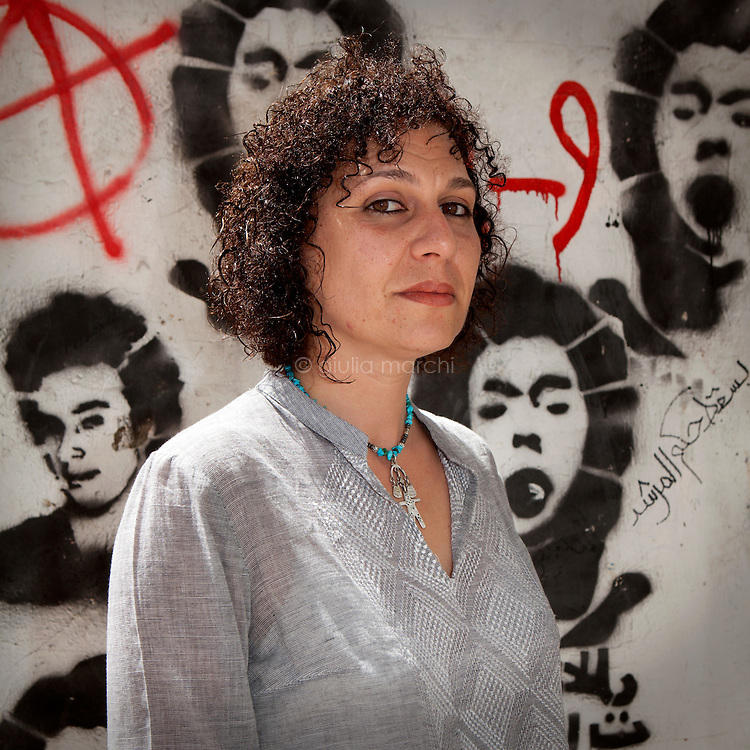 """Egypt / Cairo / 6.4.2013 / Heba Helmy, Egyptian grafic designer, poses in front of graffiti representing martyrs in Mohamed Mahmoud Street in Downtown, Cairo. Heba documented the street art in the book """"Martyr inside me"""" (Gowaya chahid). © Giulia Marchi"""