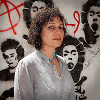 "Egypt / Cairo / 6.4.2013 / Heba Helmy, Egyptian grafic designer, poses in front of graffiti representing martyrs in Mohamed Mahmoud Street in Downtown, Cairo. Heba documented the street art in the book ""Martyr inside me"" (Gowaya chahid). © Giulia Marchi"