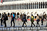 Tourists walk with boots and plastic bags to protect their shoes on flooded streets at St Mark's square during an acqua alta (high-water). The Acqua Alta, a convergence of high tides and a strong sirocco, reached 125 centimetres in Venice, on November 20, 2013.  <br /> <br /> &copy; Pierre Teyssot