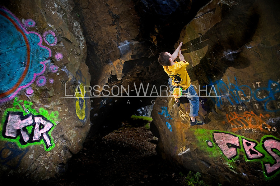 Bouldering on the graffiti covered rock at Dumbarton, Scotland