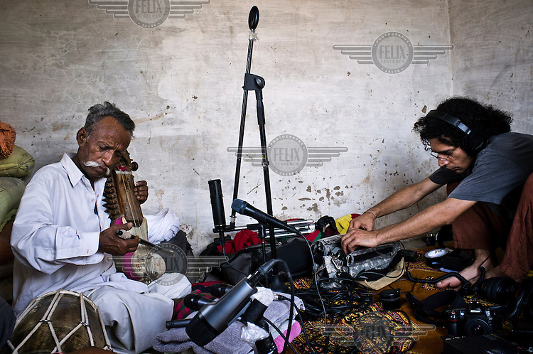 66 year old Manganiyar folk musician, Lakha Khan, plays the Sarangi (a short-necked stringed instrument) while Ankur Malhotra a technician working for 'World Music' company Amarrass Records makes a recording at Khan's home in Raneri Village.