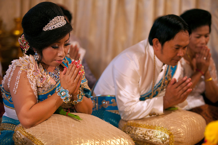 Bride and groom pray at a small village wedding outside of Phnom Penh, Cambodia. <br /> <br /> Photos &copy; Dennis Drenner 2013.