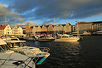 Boats at moorings and historic buildings evening light, Vagen harbour, Bergen, Norway