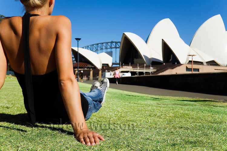 Relaxing on the lawn of the Royal Botanic Gardens in front of the Sydney Opera House.   Sydney, New South Wales, AUSTRALIA