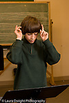 Elementary school Grade 5 arts enrichment male student conducting in music theory class vertical