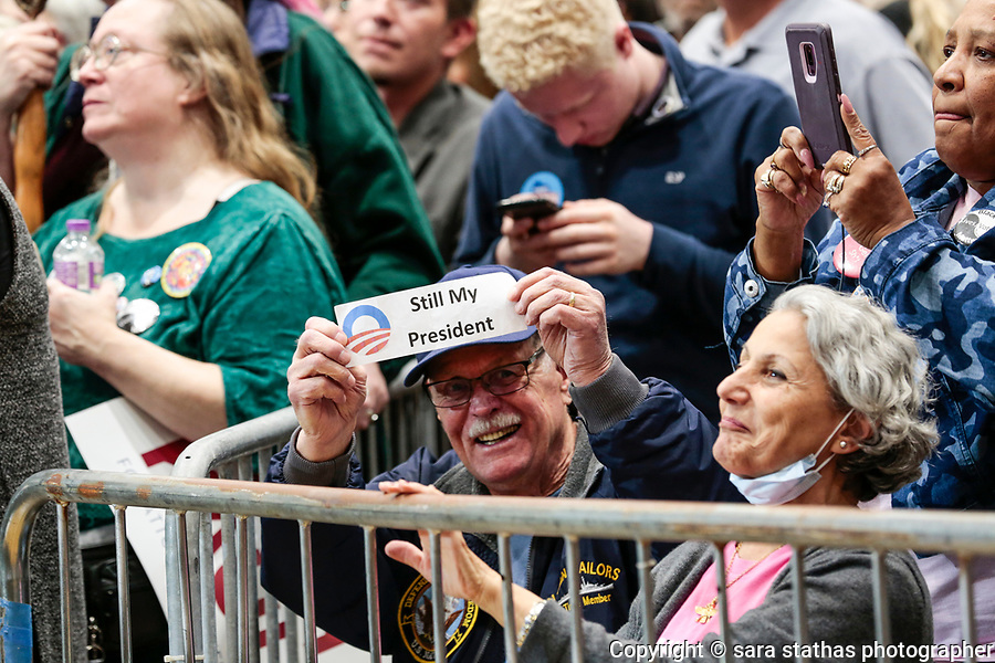 "A man holds a ""Still My President"" sign in a crowd during a rally that former president Barack Obama speaks at in Milwaukee, Wisconsin."