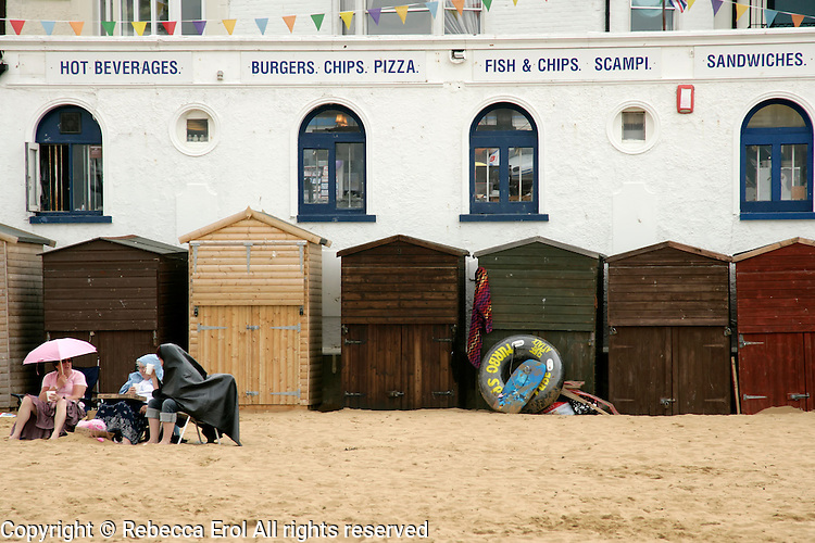 British seaside: holidaymakers sit on the beach in Broadstairs, Kent, UK, the rain