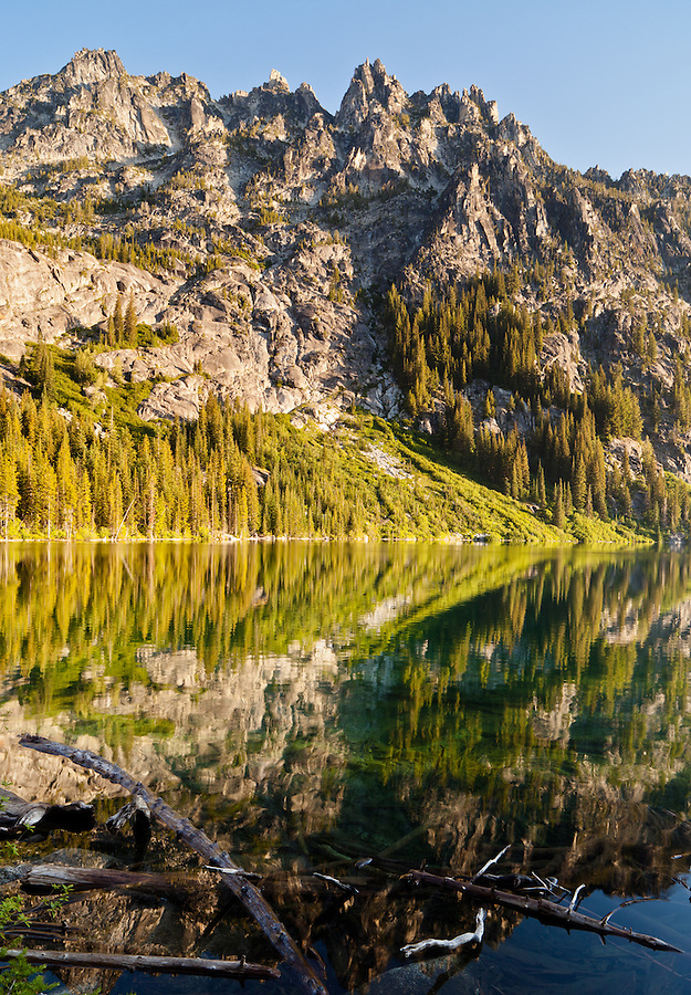 Trees and the mountains of the Enchantments reflect in the still waters of upper Snow Lake.