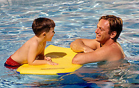 A father place with his five year old son who is floating on a Moray Boogy Board in a swimming pool.
