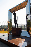 A modern statue of a musician with a guitar, framed by a silver square. Near the Millennium Bridge. In silhouette. UNK Podgorica capital. Montenegro, Balkan, Europe.