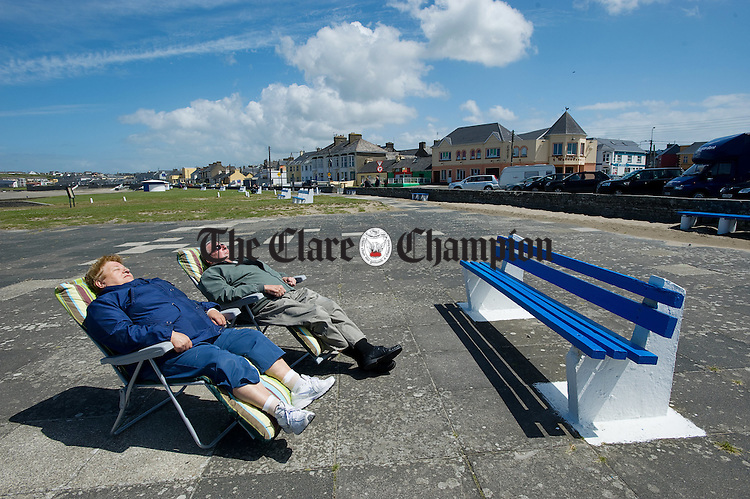 Wearing factor 1000!....Helen and Patrick Clooney of Limerick were not going to let the cool windy weather cut across their sunbathing during their recent visit to Kilkee. Photograph by John  Kelly.