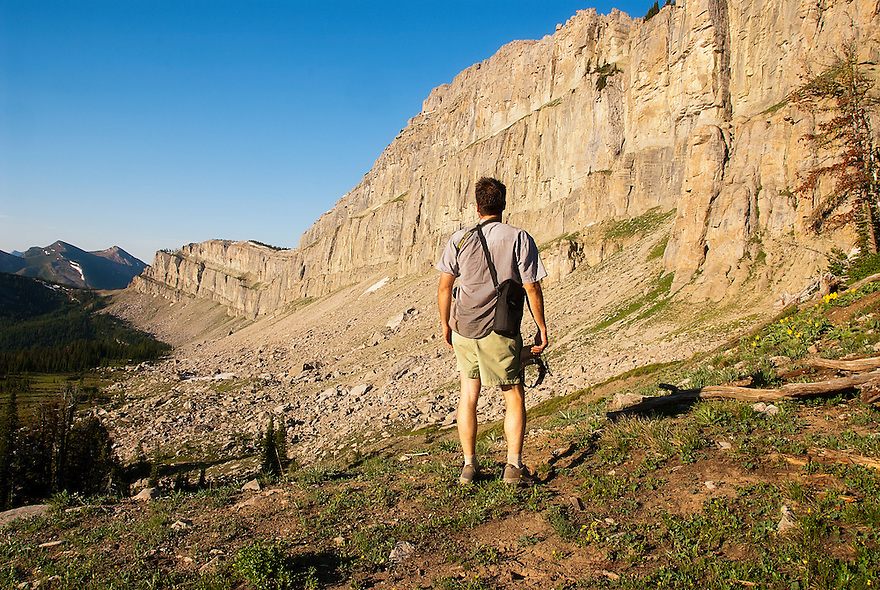 A hiker takes in the view of the Chinese Wall in the Bob Marshall Wilderness.