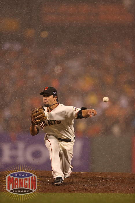 SAN FRANCISCO - OCTOBER 22:  Javier Lopez of the San Francisco Giants pitches in the rain during Game 7 of the NLCS against the St. Louis Cardinals at AT&T Park on October 22, 2012 in San Francisco, California. (Photo by Brad Mangin)