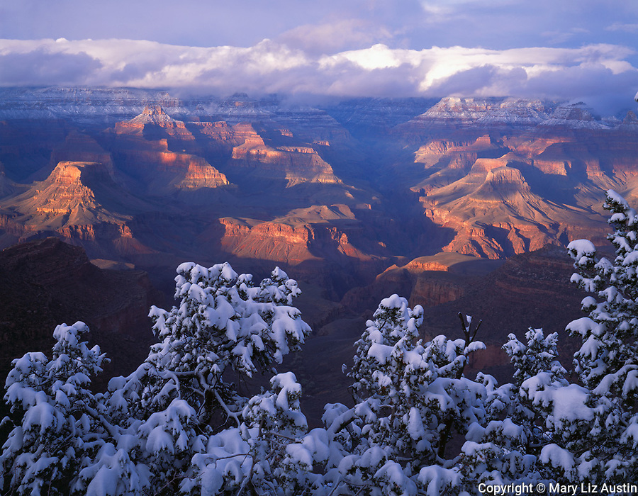 Grand Canyon National Park, AZ   <br /> Sunset light breaks through clearing winter storm clouds to light up lower canyon and North Rim from South Rim near Bright Angel trail head