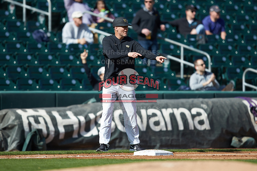 Wake Forest Demon Deacons head coach Tom Walter (16) tells a runner to stop at third base during the game against the Furman Paladins at BB&T BallPark on March 2, 2019 in Charlotte, North Carolina. The Demon Deacons defeated the Paladins 13-7. (Brian Westerholt/Four Seam Images)