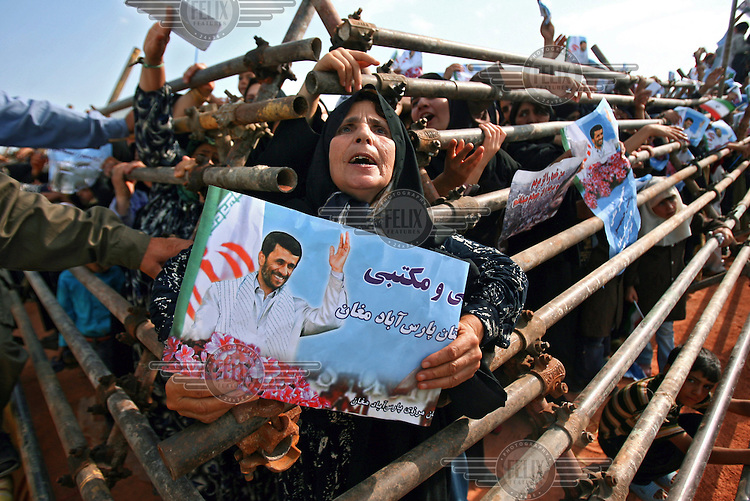 One of Iranian President Mahmoud Ahmadinejad's female supporters emerges from the barricades erected to keep people back, holding up a sign with the president's image on it, in the ethnic Turkish city of Parsabad in the Ardebil Province.