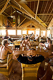 INDONESIA, Mentawai Islands, Kandui Resort,  people having a meal in the dining lodge
