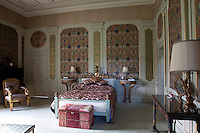 The guest bedroom called Paris is decorated with a lively mix of bright wallpaper, textiles and furnishings