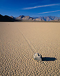 """Death Valley National Park, CA:  Tiled patterns of the Racetrack playa - a dried lake bed with path of windblown """"moving"""" rock in afternoon sun"""