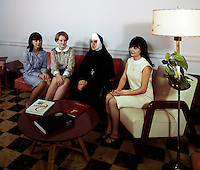 Nun sitting with young students.