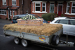 © Joel Goodman - 07973 332324 . 6 December 2013 . Marple , UK . The coffin is driven on the trailer from Marple Bridge to the The Royal Oak pub in Mellor .The funeral of farmer Bob Watson . His son David Watson drives his father's coffin on a trailer hooked to the back of Bob's favourite tractor through Marple via Bob's local pub before taking it on to the church . Photo credit : Joel Goodman