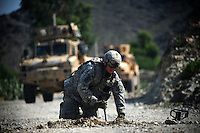a US soldier from 103rd Mountain Division - (Route Clearance Patrol),  digs through dirt looking for an IED on a main road in the Kunar Valley near the Pakistan border.
