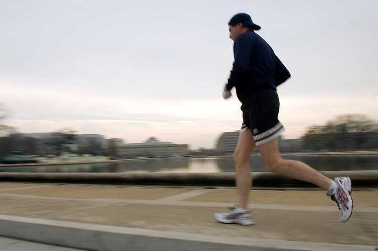 A lunch time runner enjoys the spring like weather on the West Front of the U.S. Capitol along the reflecting pool, December 10, 2007.