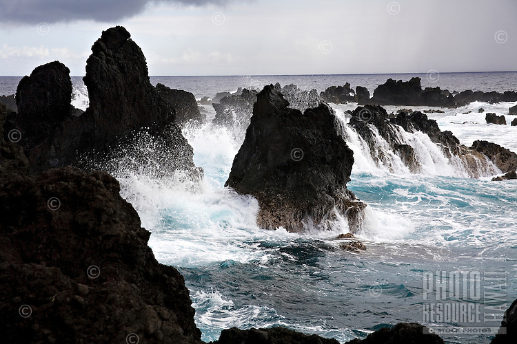 Surf crashing on rocks during incoming storm on the Big Island at Laupahoehoe