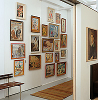 A collection of framed oil paintings lines the wall of the hall