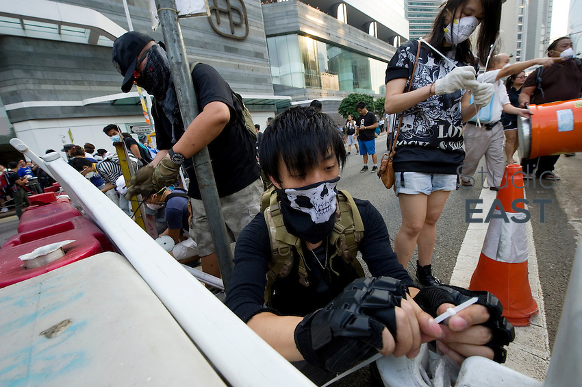 HONG KONG, HONG KONG SAR, CHINA - OCTOBER 13: Pro-democracy protesters rebuild barricades after police and masked men removed the ones they previously erected in front of Pacific Place shopping mall in Queensway, Admirality, Hong Kong, China, on October 13, 2014. Hundreds of men attempted to break through barricades erected by Hong Kong pro-democracy protesters near the city's business district, as a third week of rallies tried the patience of truck and cab drivers. 'Occupy Central' protesters rebuilt barricades to make sure Queensway stayed theirs. The 'Umbrella revolution' or 'Occupy Central' is a civil disobedience movement that began in response to China's decision to allow only Beijing-vetted candidates to stand in the city's 2017 election for the top civil position of chief executive. Thousands of pro-democracy supporters are calling for open elections and the resignation of Hong Kong's Chief Executive Leung Chun-ying. (Photo by Lucas Schifres/Getty Images)
