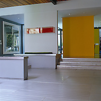 A yellow floating partition wall provides a splash of colour in this grey entrance hall with polished concrete floors