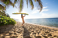 At sunset, a young woman with a standup paddleboard balanced on her head walks under a palm tree into calm waters along the North Shore of O'ahu.