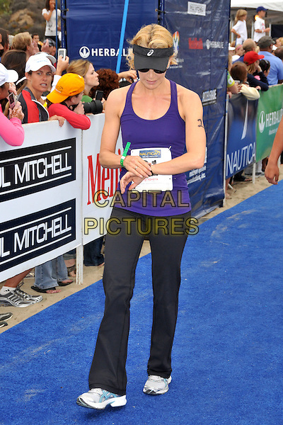 FELICITY HUFFMAN.23rd Annual Nautica Malibu Triathalon held at Zuma Beach, Malibu, California, USA..September 13th, 2009.full length sport black purple tank viser sunglasses shades shorts top tracksuit joggers checking watch wrist time.CAP/ADM/BP.©Byron Purvis/AdMedia/Capital Pictures.