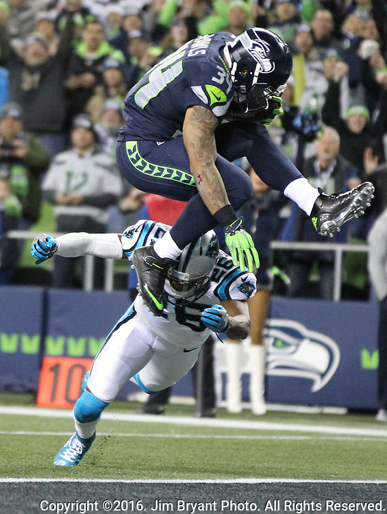 Seattle Seahawks running back Thomas Rawls (34) hurdles Carolina Panthers cornerback Daryl Worley (26) on his way to a 8-yard touchdown in the first quarter at CenturyLink Field in Seattle, Washington on December 4, 2016.  Rawls score two touchdowns in the Seahawks 40-7 win over the Panthers.  ©2016. Jim Bryant photo. All Rights Reserved.