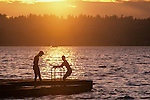 Lake Washington sunset with boys on dock silhouetted Kirkland Washington State USA.