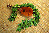 "Kamaka """"Pineapple"""" ukulele with maile lei on a lauhala mat"