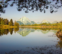 Grand Teton Mountains mirrored in still waters of Snake River just after dawn, framed by overhanging evergreen branches. Jackson Hole, Wyoming, August 2007.
