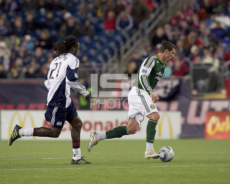 Portland Timbers forward Kenny Cooper (33) dribbles as New England Revolution midfielder Shalrie Joseph (21) closes. In a Major League Soccer (MLS) match, the New England Revolution tied the Portland Timbers, 1-1, at Gillette Stadium on April 2, 2011.