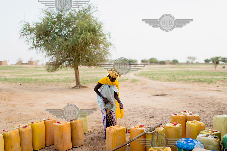 A woman preparing to carry two heavy containers of water home from a well.