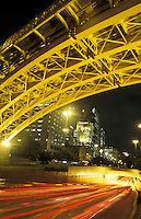 Yellow metallic structure of Santa Efigenia Viaduct in downtown Sao Paulo at night seen from below at street level - urban life - traffic lights, cars entering underground tunnel and corporate buildings, Brazil.