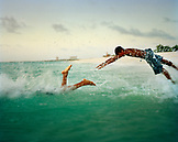 ARUBA, boys running and diving in the Caribbean Sea, Eagle Beach