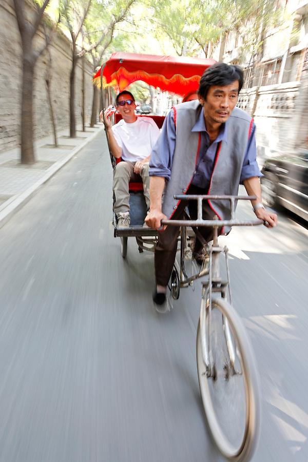 A pedicab driver gives a tourist a rickshaw ride through a Beijing hutong, Beijing, China, Asia