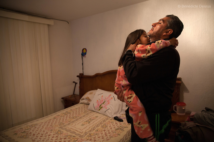 """Donovan gives a hug to his daughter before she goes to sleep at their home in Texcoco, Mexico on February 1, 2016. Donovan Tavera, 43, is the director of """"Limpieza Forense México"""", the country's first and so far the only government-accredited forensic cleaning company. Since 2000, Tavera, a self-taught forensic technician, and his family have offered services to clean up homicides, unattended death, suicides, the homes of compulsive hoarders and houses destroyed by fire or flooding. Despite rising violence that has left 70,000 people dead and 23,000 disappeared since 2006, Mexico has only one certified forensic cleaner. As a consequence, the biological hazards associated with crime scenes are going unchecked all around the country. Photo by Bénédicte Desrus"""