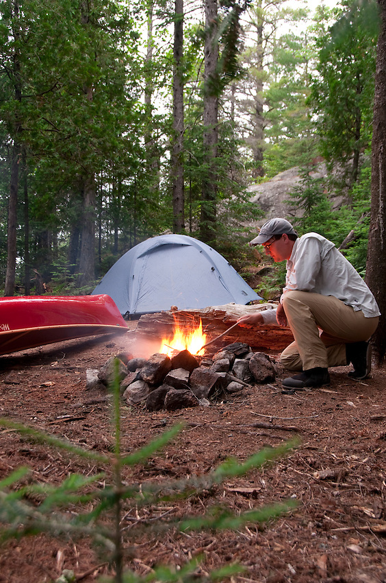 A canoeist and campsite with campfire at Craig Lake State Park near Michigamme Michigan.