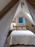 A double bed has been tucked under the ancient A-frame of the attic and draped with black-and-white ticking